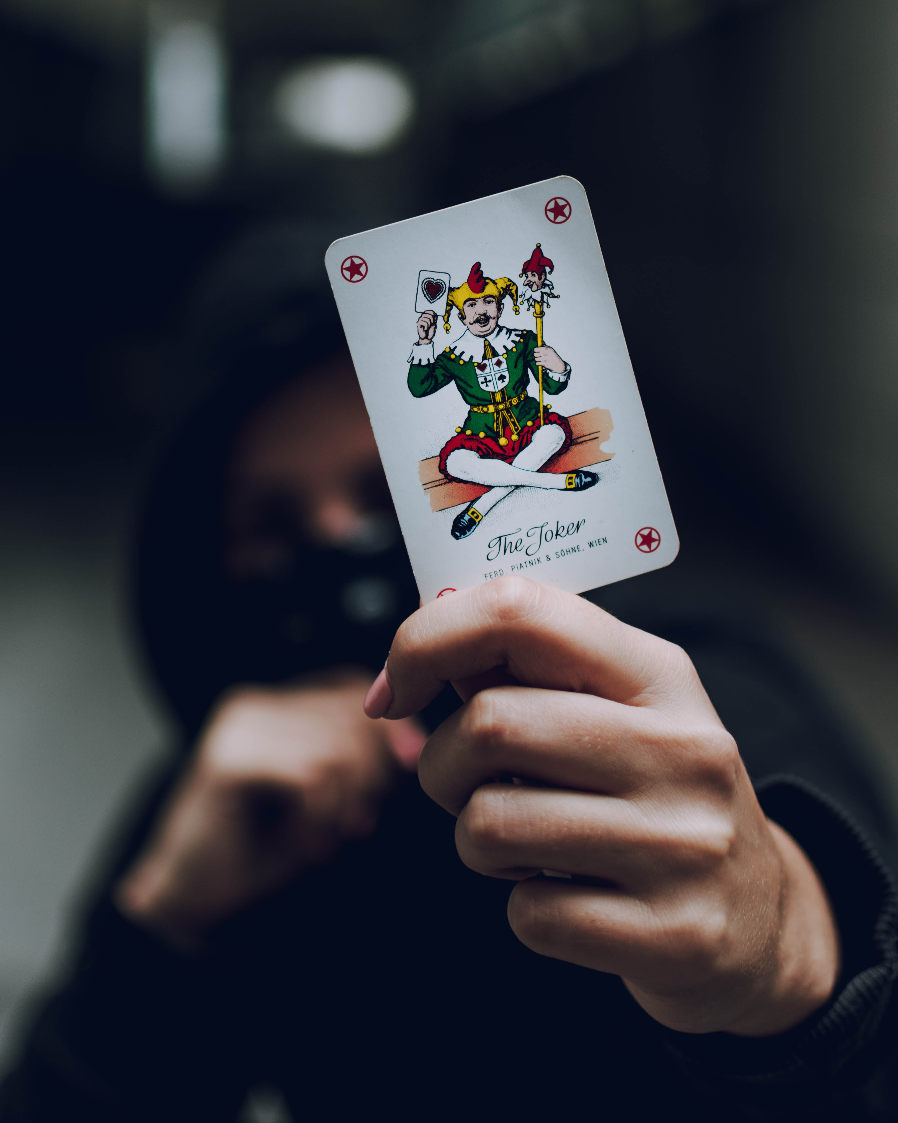 Selective Focus Photo Of Person Holding Joker Playing Card