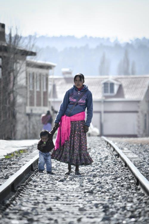 Woman Holding Toddler While Walking on Railway