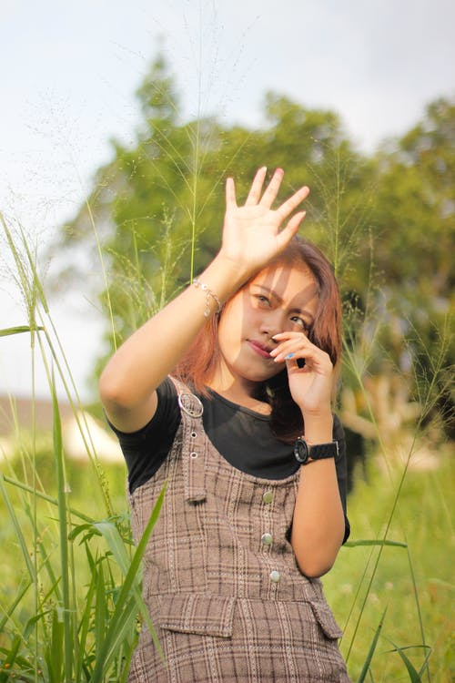 Woman Standing in Grass Field Covering Her Face from Sunray