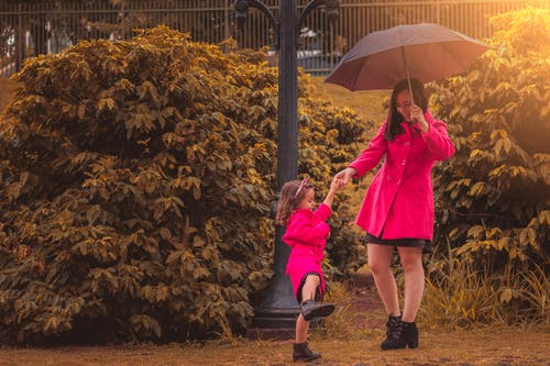 Woman Holding Umbrella While Holding Girl's Hand