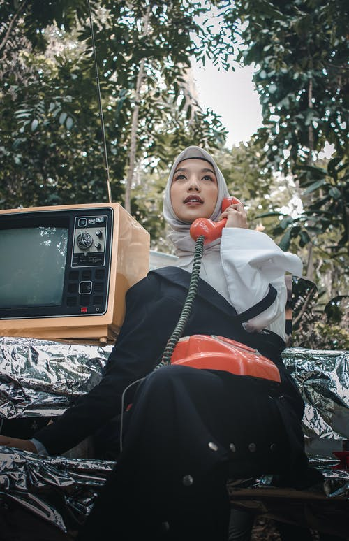 Low Angle Photo of Muslim Woman in a Hijab Sitting on a Bench Posing With a Rotary Phone and an Old Television Set Beside Her