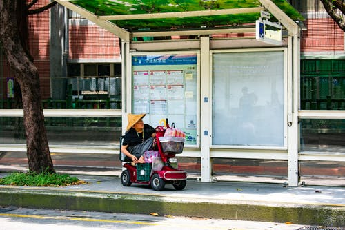 Man Riding  Electric  Wheel Chair Near Concrete Road