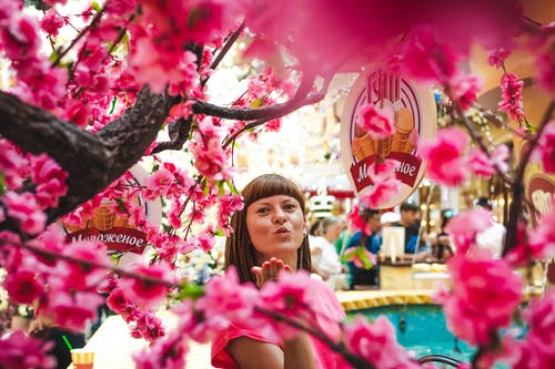 Photo of Woman Standing and Making Flying Kiss by Blooming Pink Cherry Blossoms