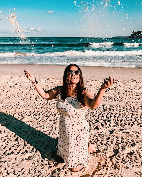 Woman Kneeling On Sand Under Blue Skies