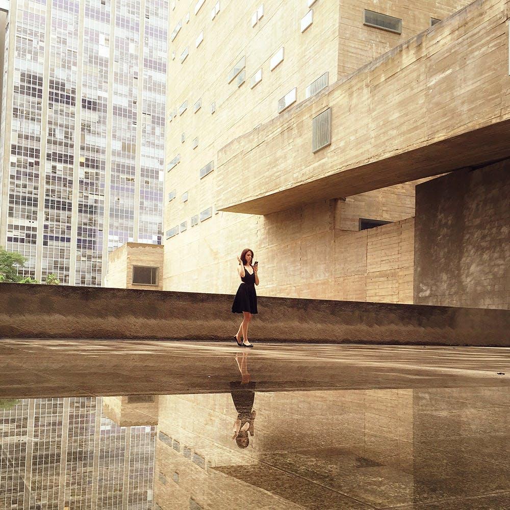 Woman Wearing Black Mini Dress Standing on the Concrete Floor