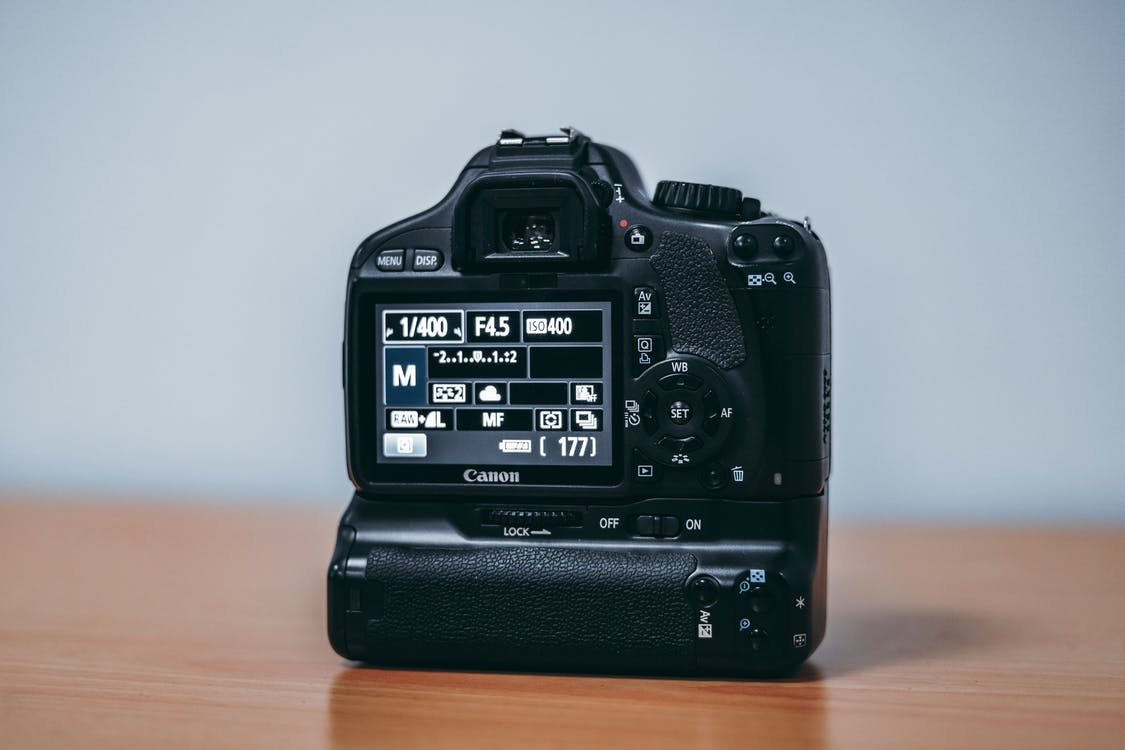 Black Canon Dslr Camera on Wooden Table