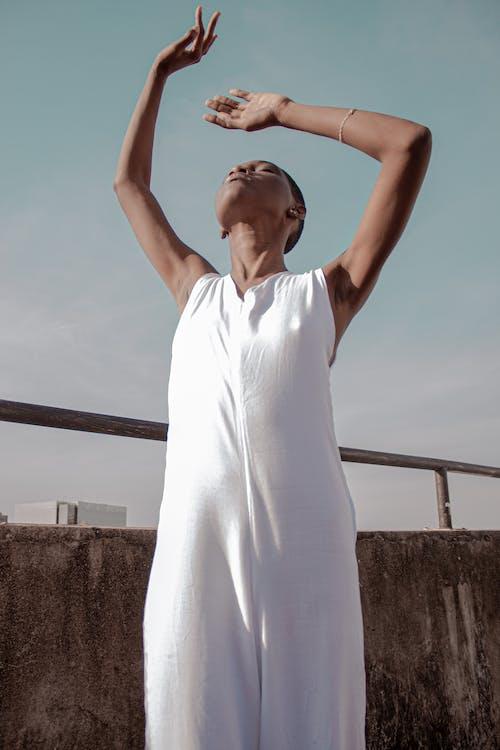 穿着白色连衣裙的女人摆姿势与她的头和她的手的照片