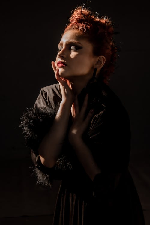 Photo of Woman in Black Long-sleeved Dress Posing With Her Eyes Closed In Front of Black Background