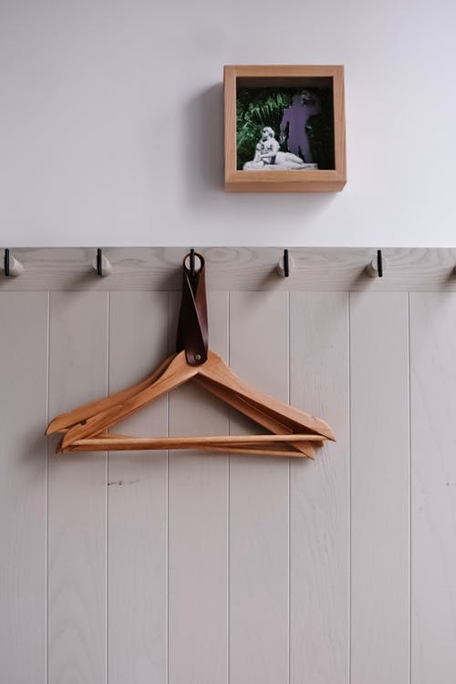 Hanged Brown Wooden Hangers Near Square Brown Wooden Photo Frame