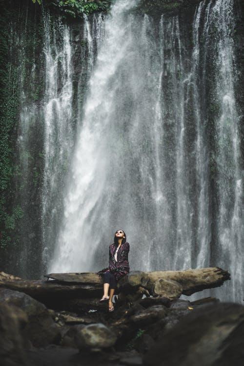 Woman Sitting Fallen Tree Trunk In Front Of A Waterfalls