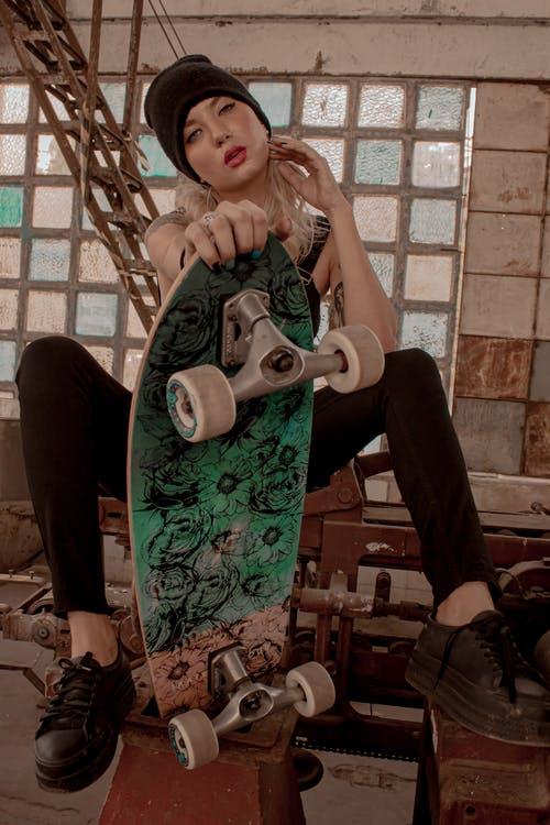 Photo of Sitting Woman in Black Outfit and Black Beanie Posing While Holding Skateboard