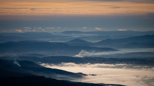 Mountains in fog under cloudy sky at sundown