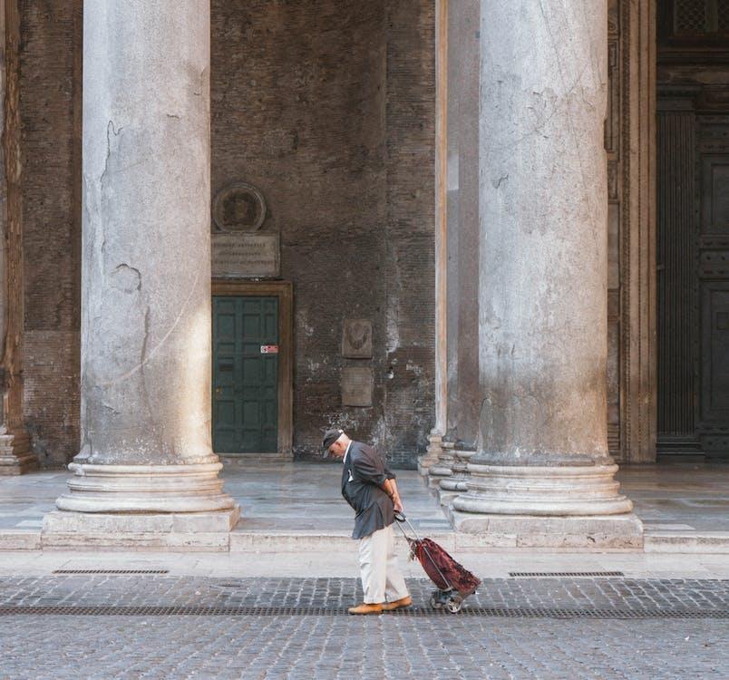 Man Walking And Pulling Trolley Bag Beside Building
