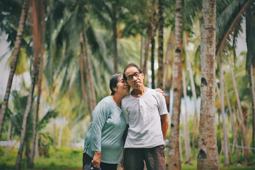 Selective Focus Photo of Old Couple Standing Together With Trees in the Background