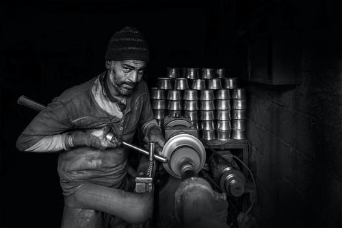 Gray-scale Photo of Man Making Cups