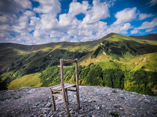 A Worn Down Wooden Chair On Top Of A Hill Surrounded By Green Mountains