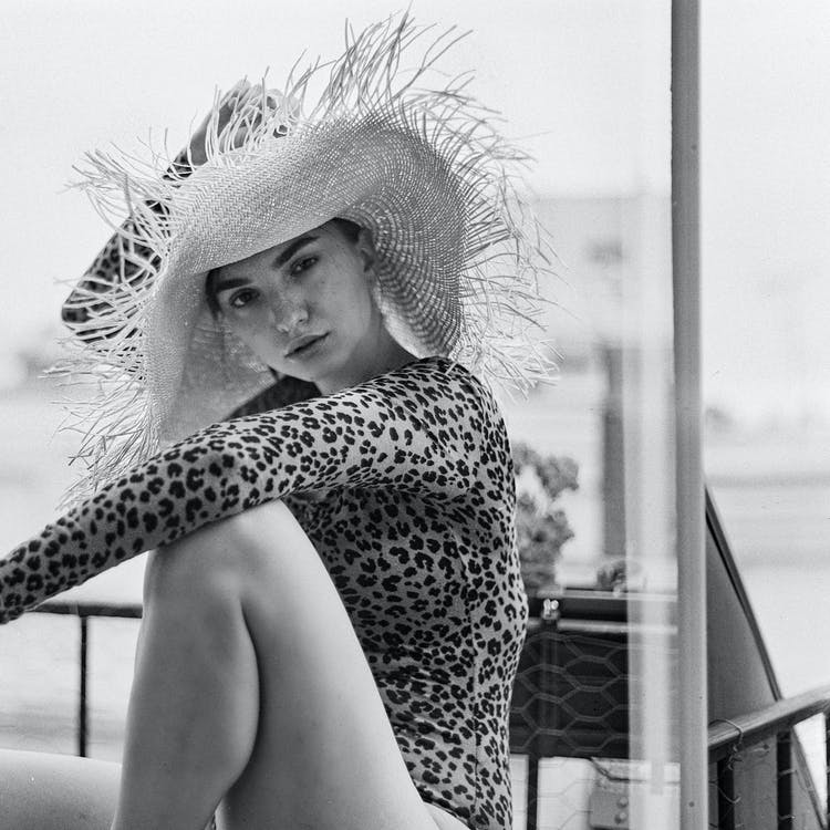 Grayscale Photo of Woman in Straw Hat and Leopard Print Bodysuit