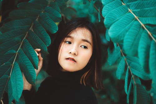 Girl Wearing Black Turtle-neck Top Surrounded by Green-leafed Tree