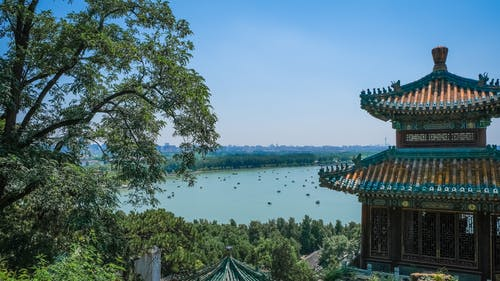 Multicolored Concrete Building  With A Lake View Showing The Distinct Architectural Design Of Ancient China