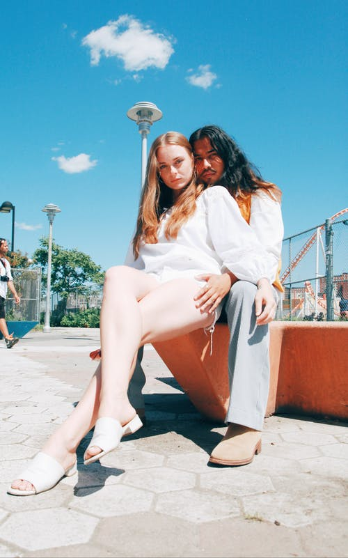 Two People Sitting In A Park