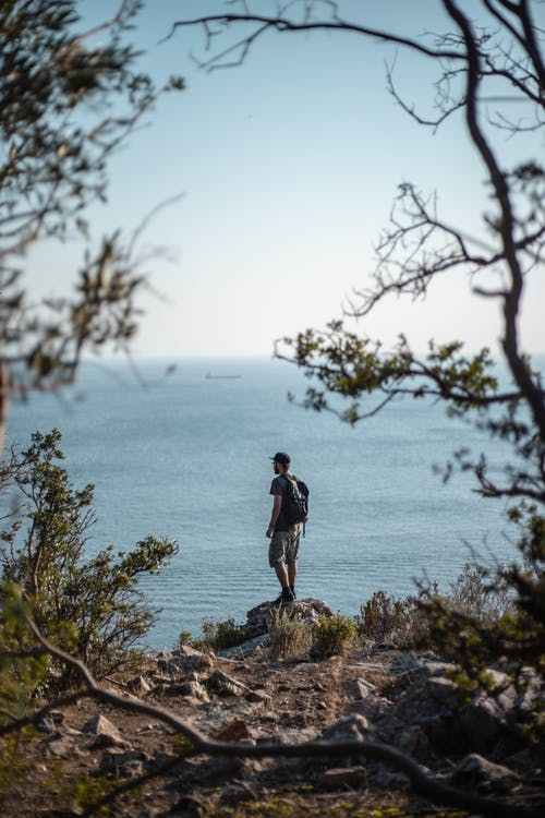 Man Standing on Rock Near Cliff