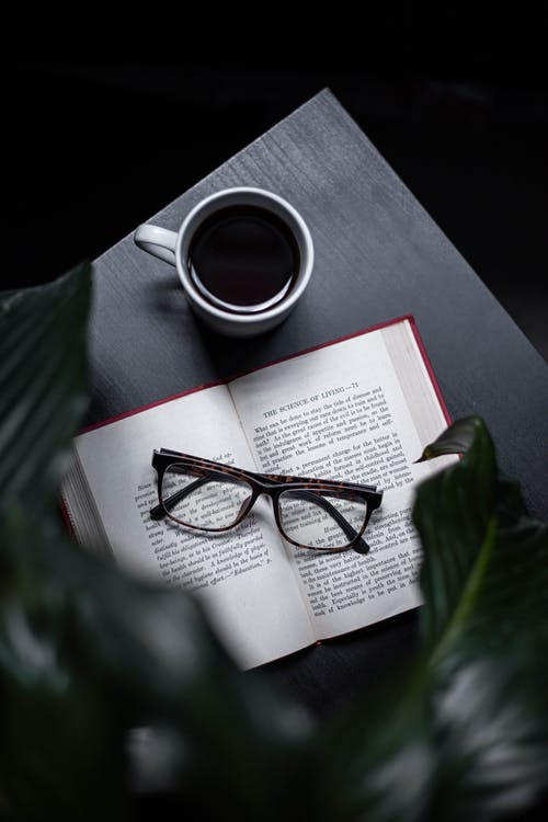 Eyeglasses On Opened Book Beside Cup Of Coffee On Table