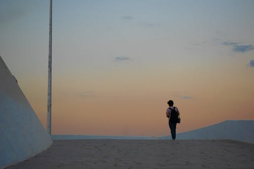 Back View Photo of Person Standing Alone During Golden Hour