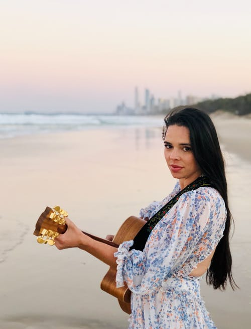 Woman Playing Acoustic Guitar On Seashore