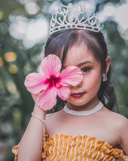 Girl Wearing A Silver Crown Holding Pink Flower