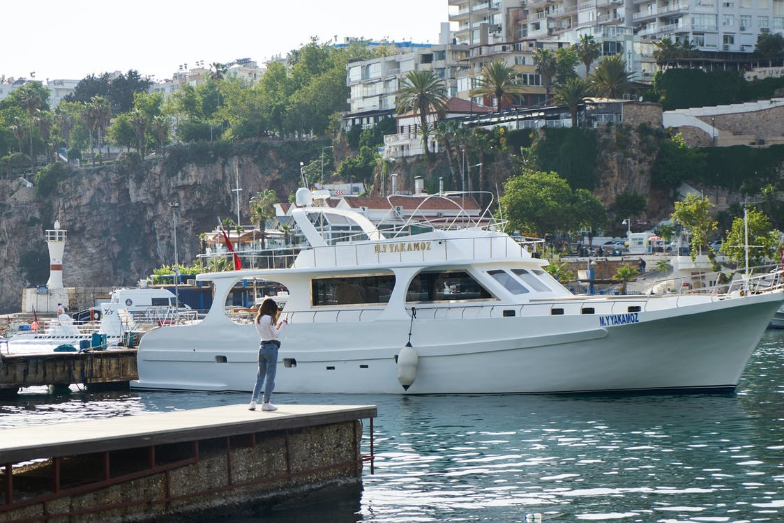Woman On A Dock Close To A White Yacht on Dock Near Island