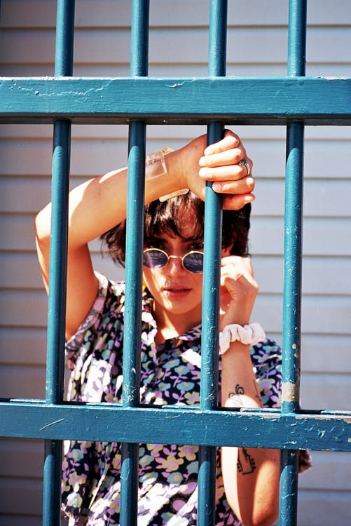 Photo Of Woman Standing Behind Blue Bars