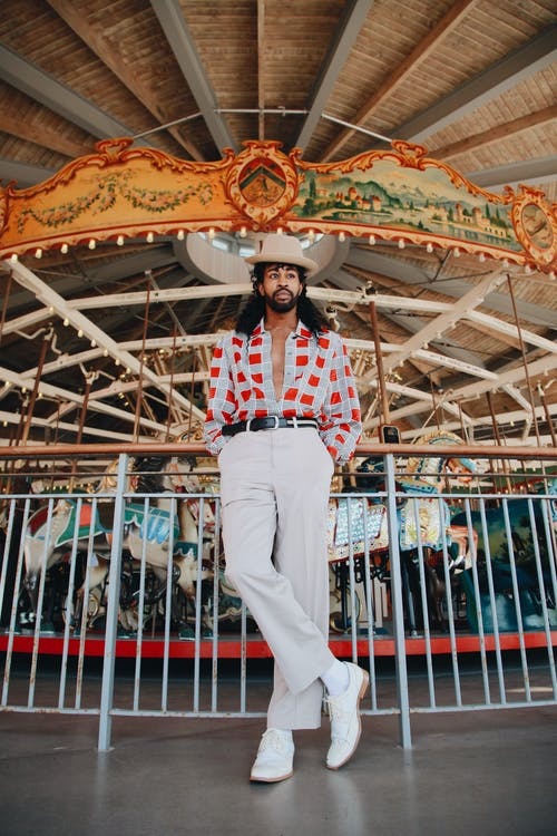 Photo Of Man Standing In Front Of Carousel