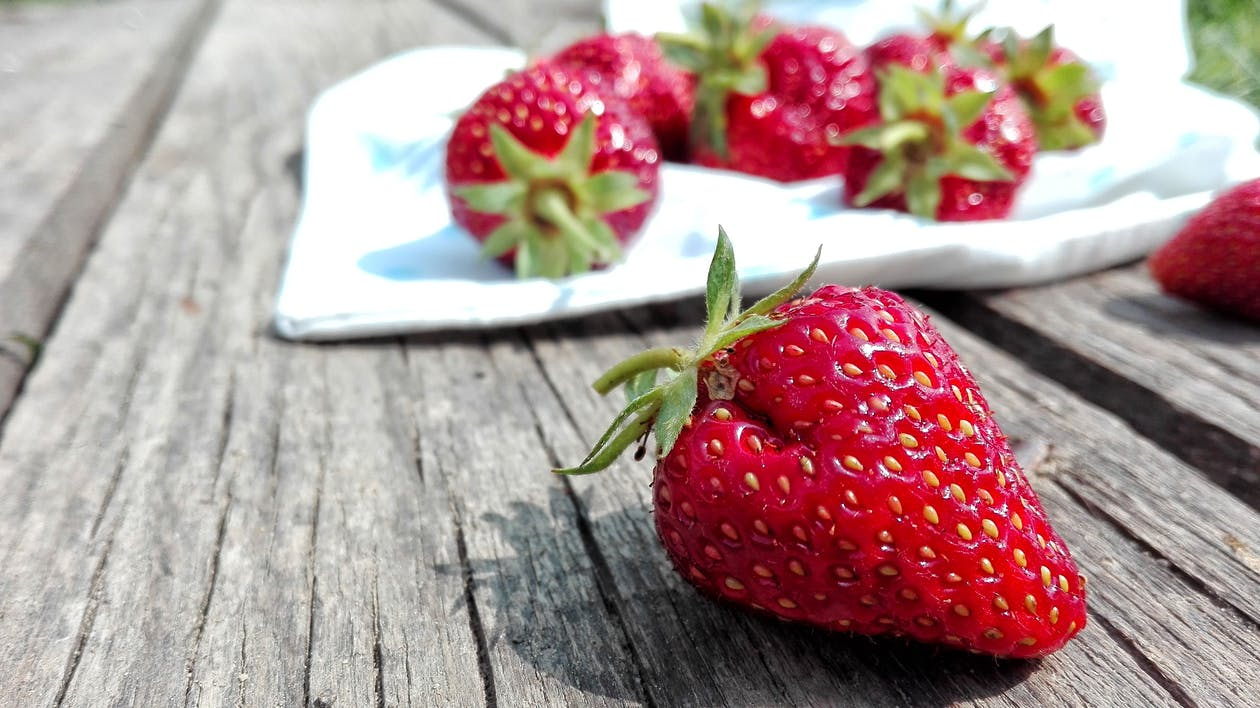 Strawberries on Top of Brown Table