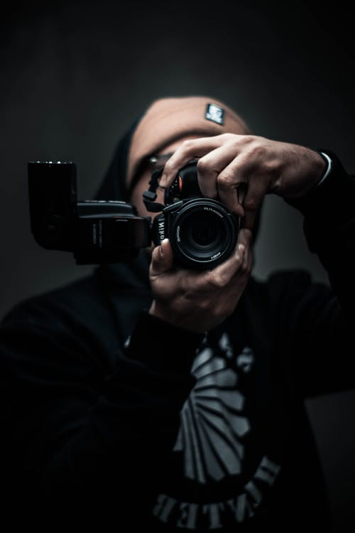 Man in Black Hoodie Using a Black Camera