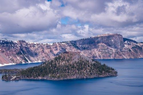 Island Near Mountain Under Cloudy Sky