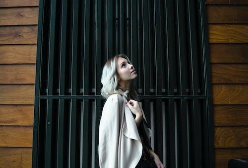 Side View Photo of Woman in White Coat Standing In Front of Black Metal Door Looking Up