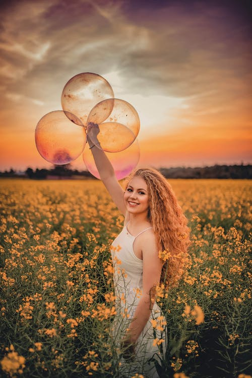 Woman Standing in Yellow Flower Field Holding Balloons