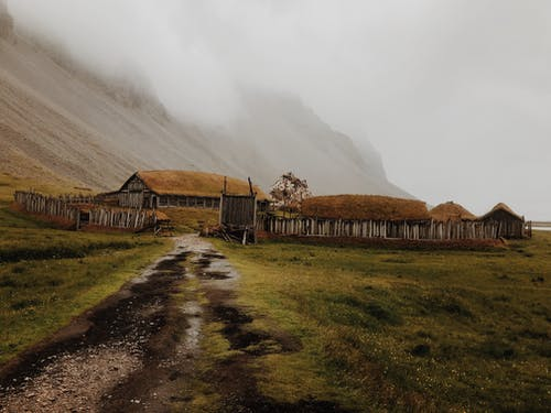 Cottage Houses Below A Foggy Mountain