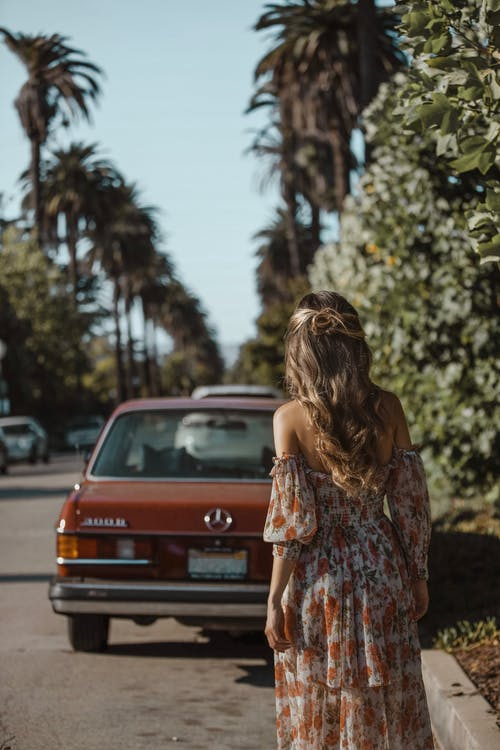 Woman Standing Behind Vehicle Parked On Side Of Road