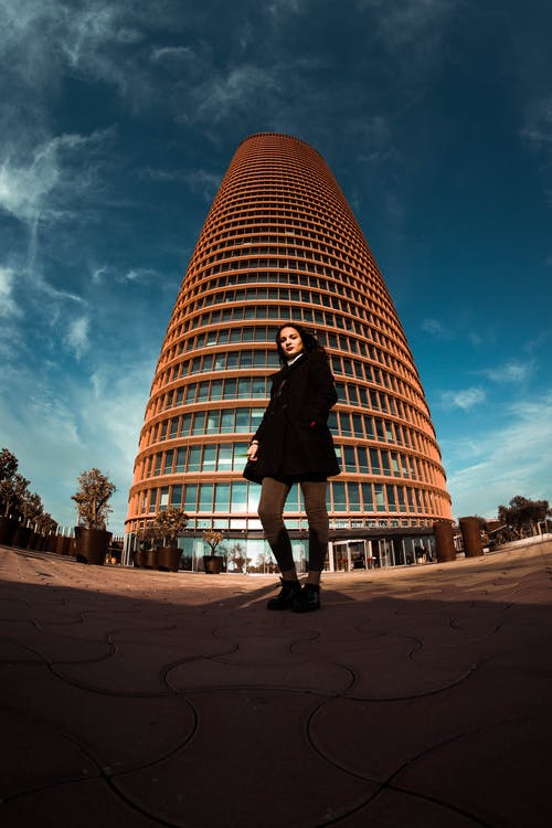 Fish-Eye Photography of Woman Standing in Front of Tall Building