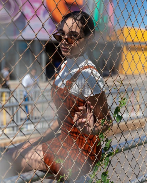 Photo Of Woman Sitting Beside Chain Link Fence