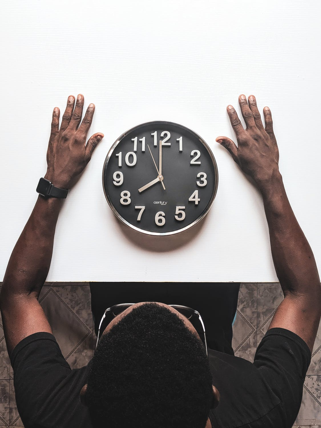 man sitting in front of a clock on a table