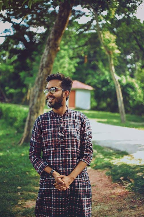 Kostenloses Stock Foto zu grüner baum, man lächelt, mann mit brille