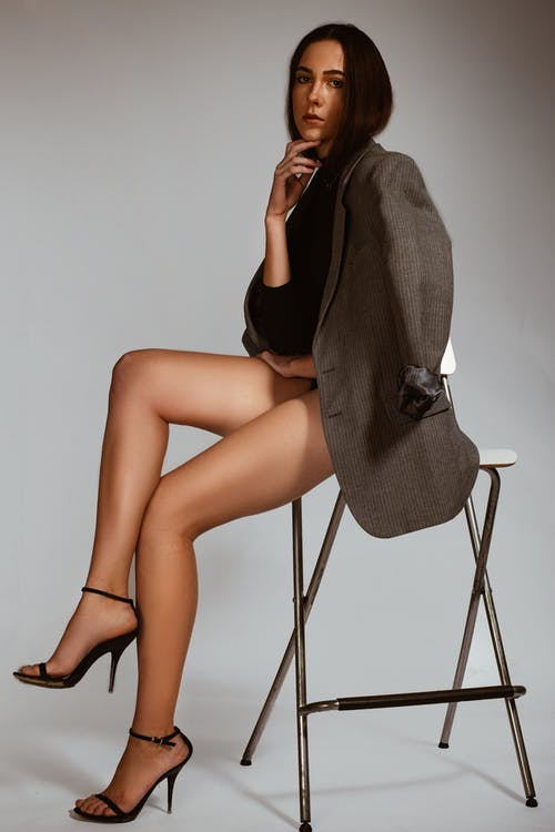 Photo of Woman in Gray Blazer and Black Top Sitting on Bar Stool Posing