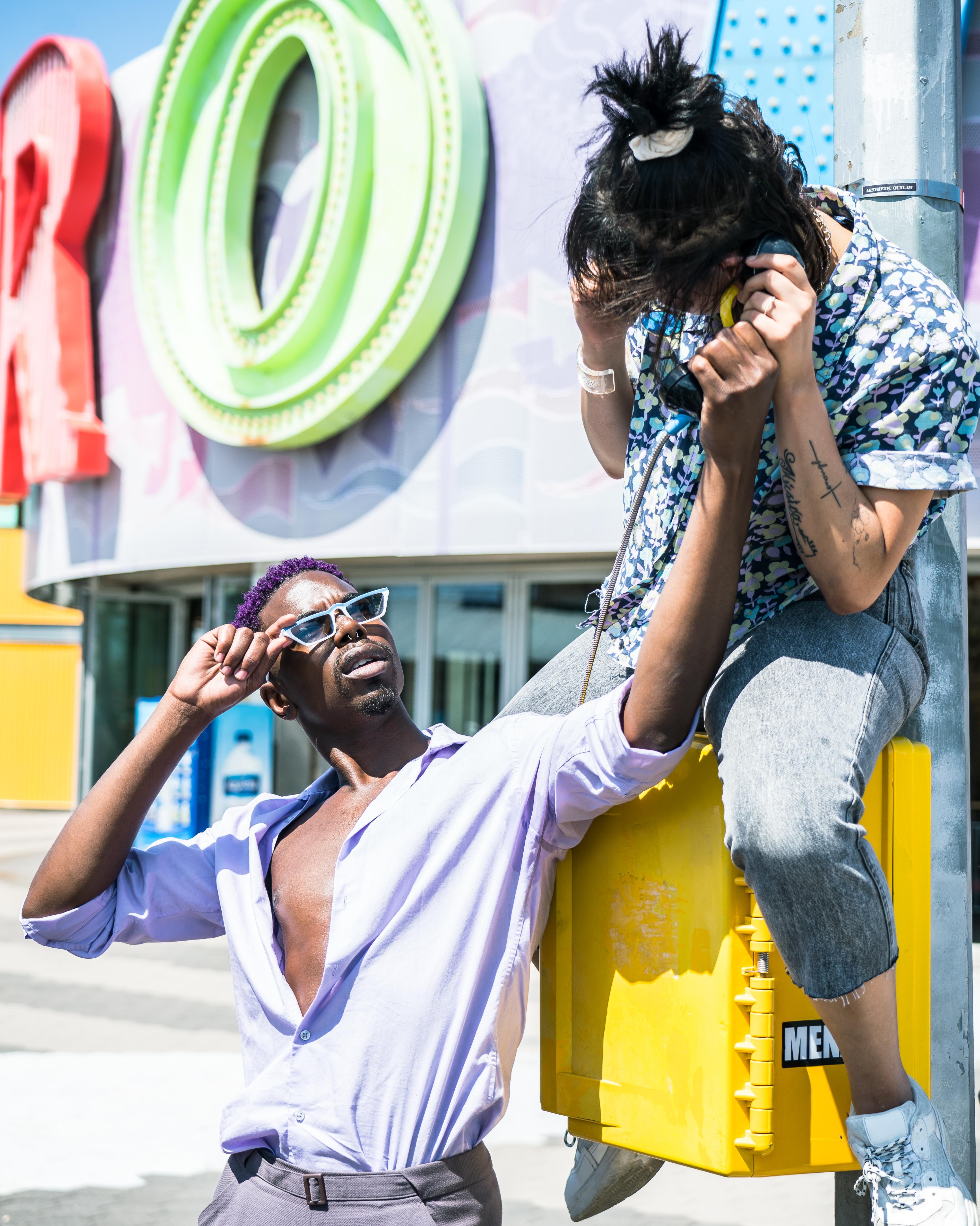 Man Wearing Purple Dress Shirt Leaning on Wall Near Woman Sitting