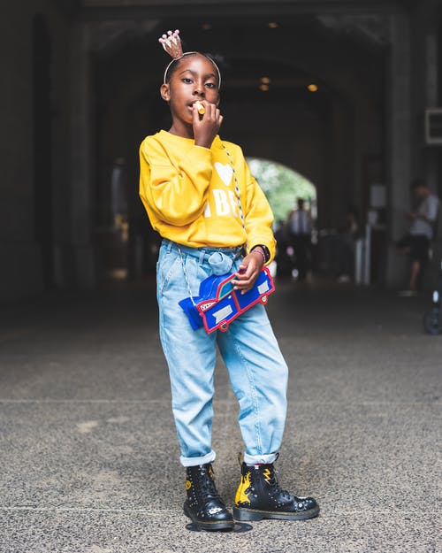 Photo of Girl in Yellow Sweatshirt, Blue Jeans, and Black Posing Alone While Applying Lip Balm