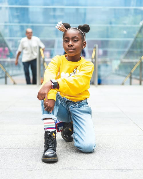 Selective Focus Photo of Girl in Yellow Sweatshirt, Blue Jeans, and Black Leather Boots Posing Alone While Kneeling