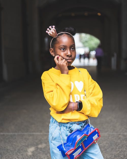 Selective Focus Photo of Girl in Yellow Sweatshirt, Blue Jeans, and, Black Leather Boots Posing While Looking Away