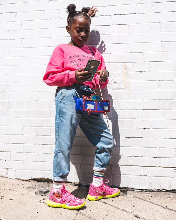 Photo of Young Girl in Pink Sweatshirt and Blue Jeans Standing and Leaning on Wall While Using a Smartphone