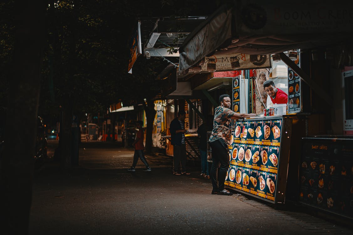 Man Standing In Front Of Food Stall